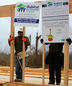 Michael Bredemeyer, left, helps raise the first wall of his new house.