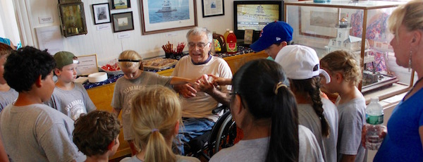 Retired teacher Bob Jester gives a lesson in induction at the grand opening of the seaport museum's room named in his honor.