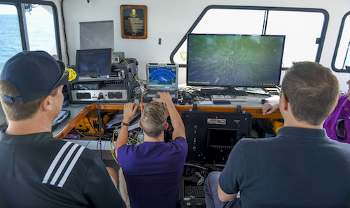 Art Trembanis, a researcher at the University of Delaware, Ken Haulsee, a graduate student at UoD and Alexis Catsambis, Ph.D., an underwater archaeologist at the Naval History and Heritage Command, left to right, monitor incoming video from a remotely operated vehicle. | U.S. Navy photo by George Schwarz, Ph.D.