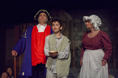 Mr. Bumble (Rick Peters) and Widow Corney (Kimet Speed) of the workhouse try to decide what to do with Oliver