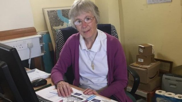Photo of Sister Christine Frost OBE of Neighbours in Poplar behind office desk