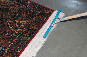 Grooming the fringe of an oriental rug