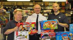 Captain Kevin Standbury and TfL staff pose with unopened toys