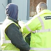 UK Border Agency officer questions workers at timberyard