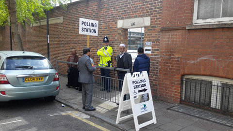 Police stand guard in front of the Kobi Nazrul Primary School in Tower Hamlets