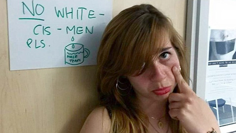 "Bahar Mustafa in front of a sign saying ""no white - cis - men"". Pic: Change.org"
