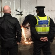 Bailiffs and council enforcement officers busting into illegal peanut-roasting shack under Fenchurch Street railway.