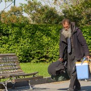 Homeless man walking through park