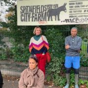 4 women and a man posing with their hands crossed and sad faces in front of Spitalfields City Farm gate