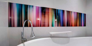 Printed striped glass splashback behind a bath