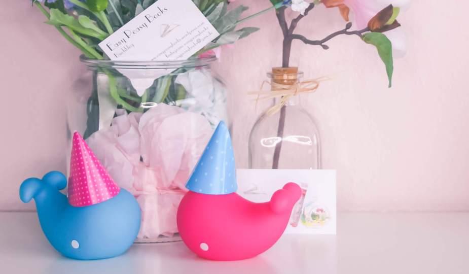 zwei plastikwale mit geburtstagshütchen