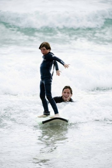Smiles for miles as Tommy instructs a determined grom. Photo courtesy of CampSurf