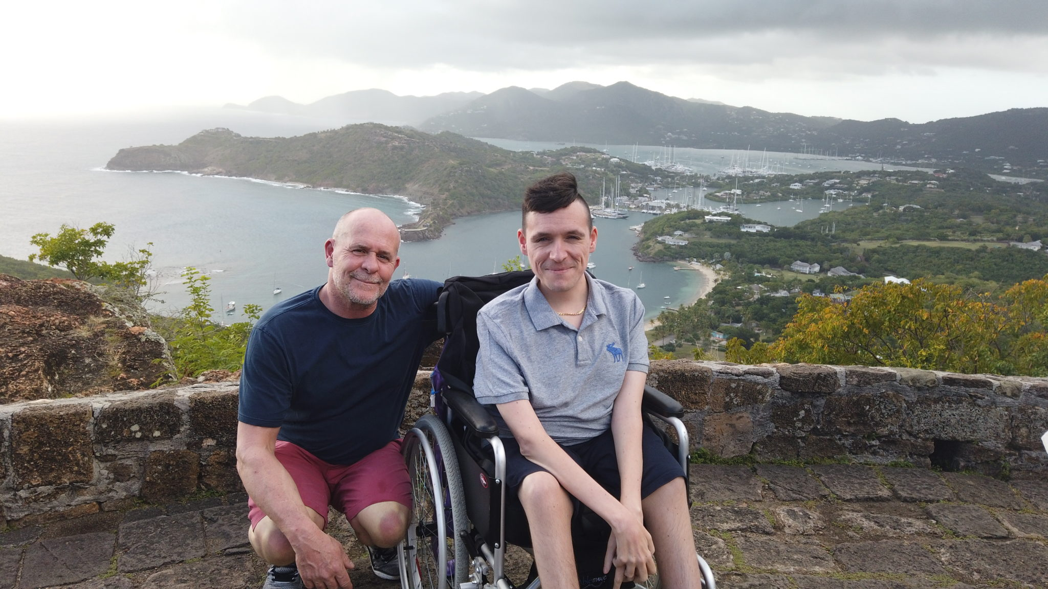 Josh's father crouched with his arm around Josh, who is sat in his manual wheelchair. Both facing the camera. In the background is Shirley Heights, with mountains, sea and harbour in the background with grey sky.