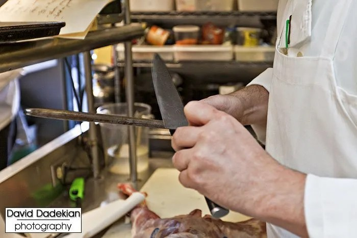 Honing knives before beginning the breakdown of the whole goat