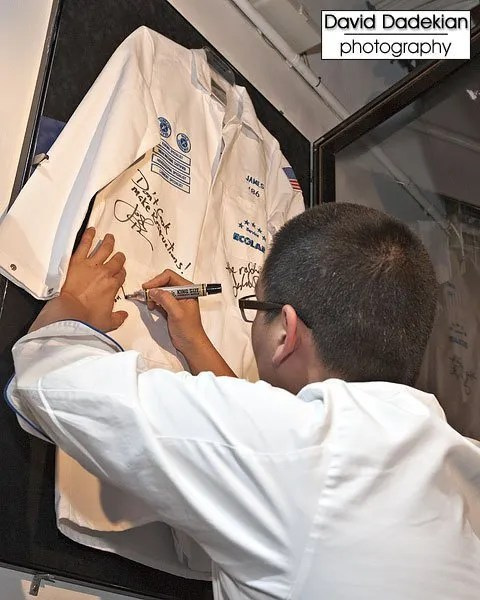 Chef de Cuisine Eric Haugen signing the framed whites at the James Beard House