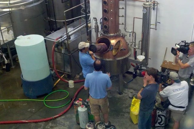 "Mike Rowe of Discovery Channel's ""Dirty Jobs"" loads low wine into a still"