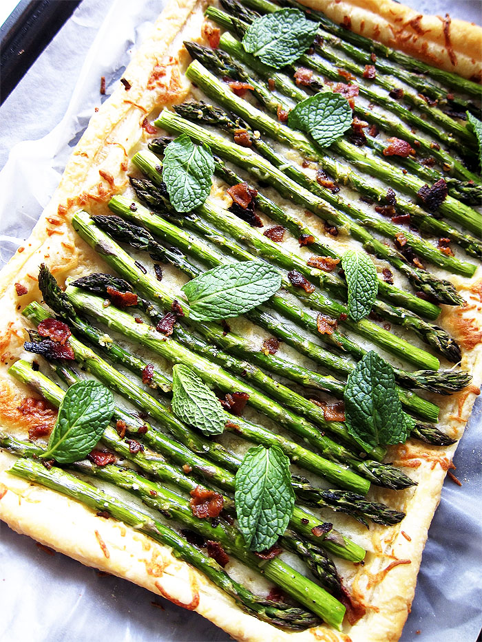 Asparagus Tart with Bacon: A buttery, crisp puff pastry layered with cheese, spicy roasted asparagus, bacon crumbles and topped with mint leaves. Perfect for brunch or an Easter appetizer.
