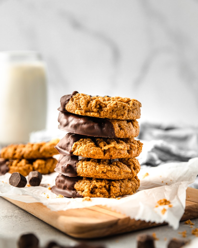 Stacked Peanut Butter Cookies dipped in chocolate laying on parchment paper