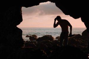 Guy Standing In Cave Near Ocean