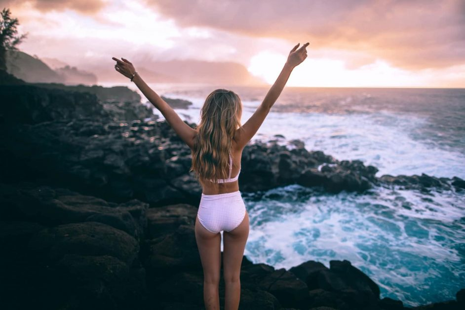 A woman raising hands in a bathing suit, as featured on a blog about healthy eating hacks