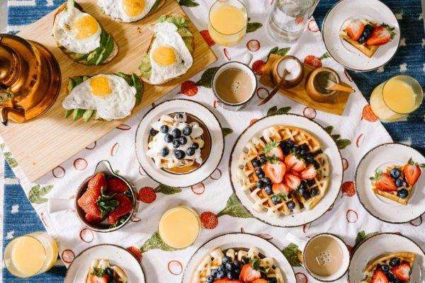 Multiple breakfast options including fried eggs, waffles, coffee, orange juice, fruit.