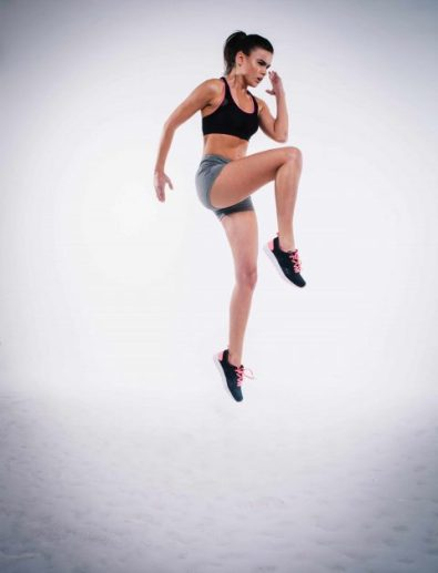 Woman doing a jump lunge in front of a white wall