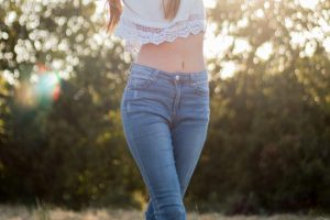 Woman Wearing White Crop Top in Blue Jeans in Field with sun behind her.