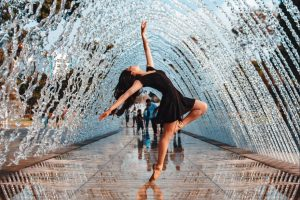 Woman in Black Dress Dancing Under Water Fountain