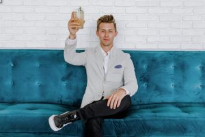 Man in White Blazer Raising Glass on Blue Couch
