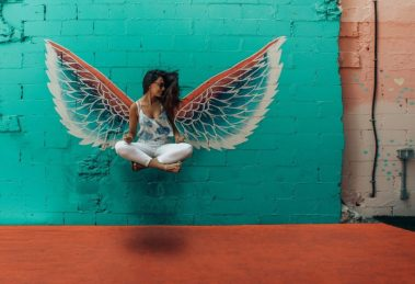 Woman Floating Legs Crossed In Front of Blue Wall with White Wings