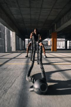Man Using Battle Ropes with Kettlebell Anchor