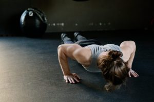 Woman Doing Pushup With Wall Ball In Background