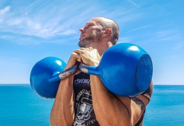 Guy Holding Two Blue Kettlebells with Ocean in Background