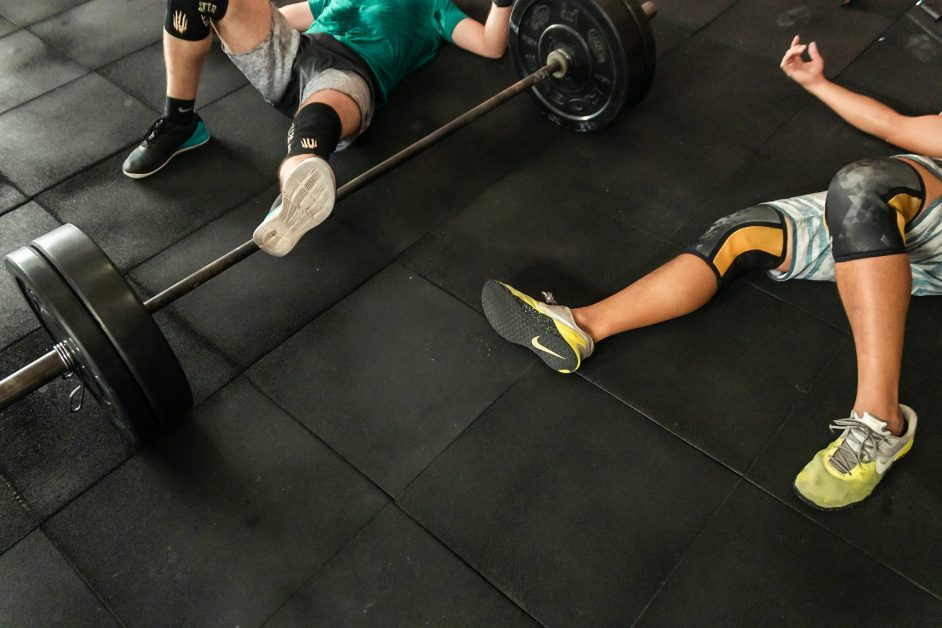 Two Athletes Laying on Floor Exhausted From Workout