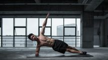 Guy Without Shirt Doing Side Plank with Arm Elevated