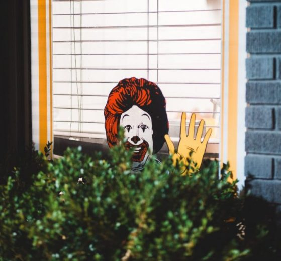 Ronald McDonald Cut Out Waiving from Above Bush