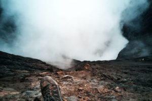 Runner Sitting at Edge of Mountain with Smoke Coming Up