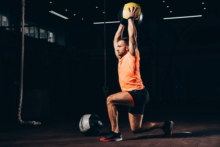 Handsome Fit Sportsman Performing Lunge With Medicine Ball Overh