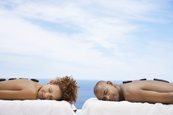 man and woman receiving hot stone therapy at spa with ocean in background