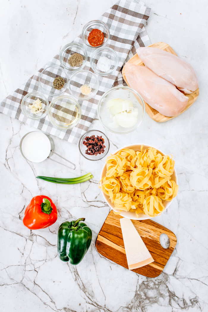 Ingredients with chicken breast, noodles and all spices for Cajun Chicken Pasta Skillet