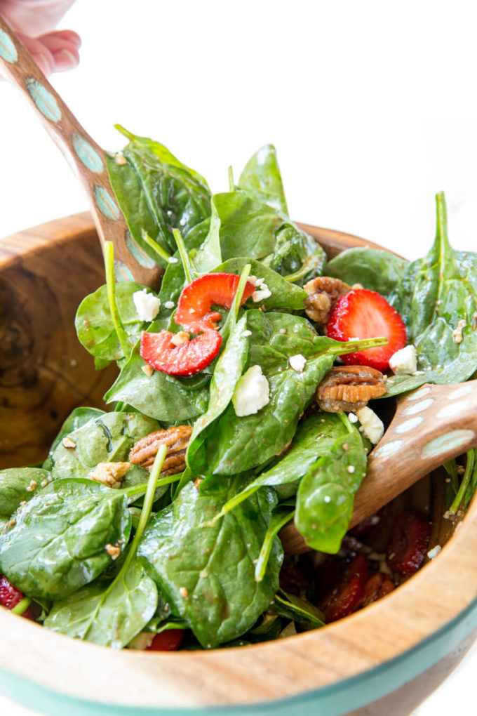 Strawberry Pecan Spinach Salad with a balsamic vinaigrette in a wooden bowl.
