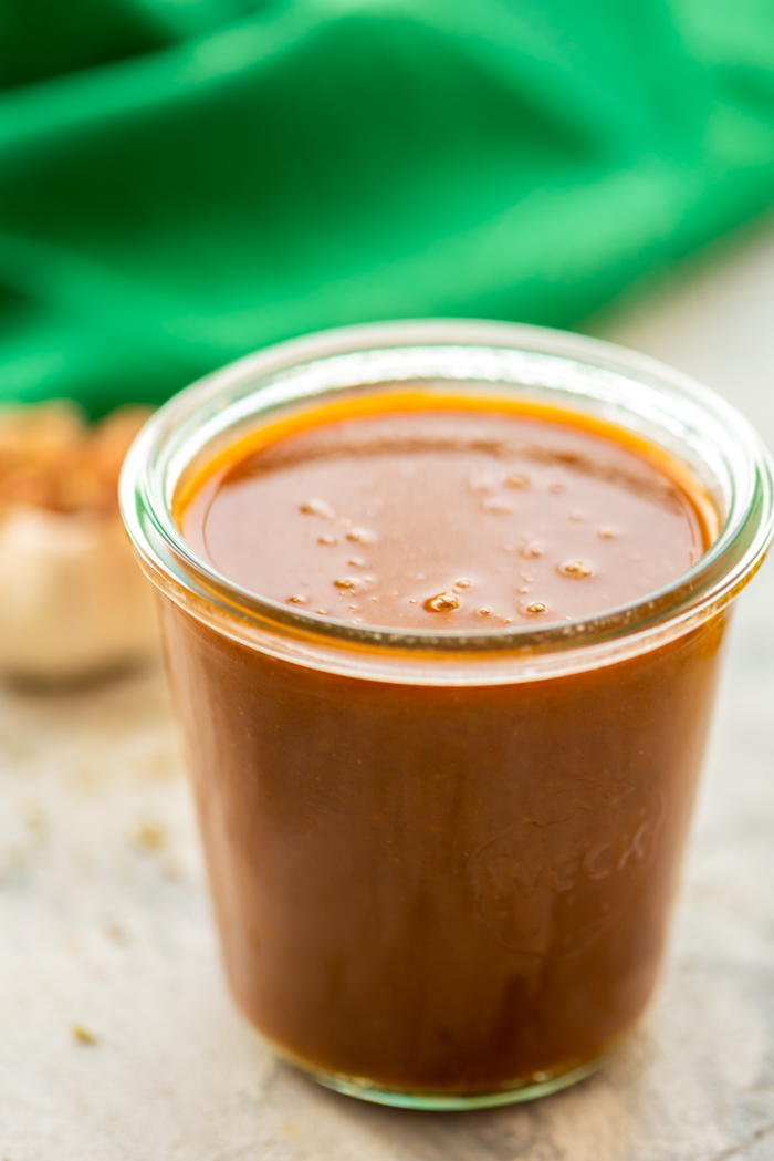 Homemade enchilada sauce in glass jar.