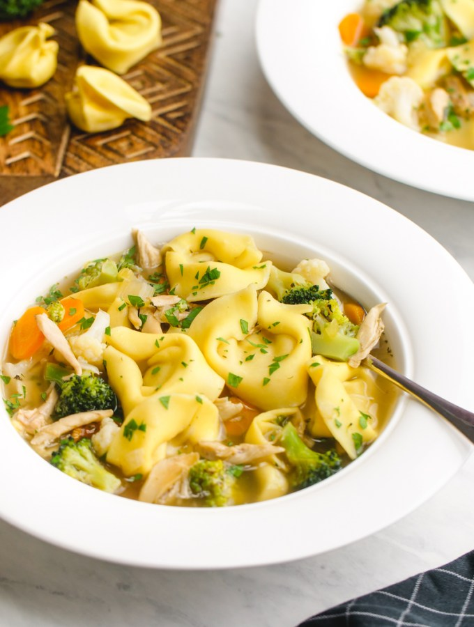 A big white bowl of chicken tortellini soup