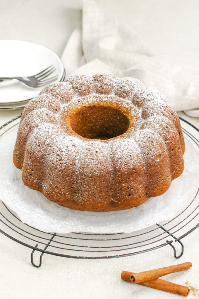 A rich and moist pumpkin bundt cake recipe, with a pumpkin bundt dusted in powdered sugar and sitting on a cooling rack