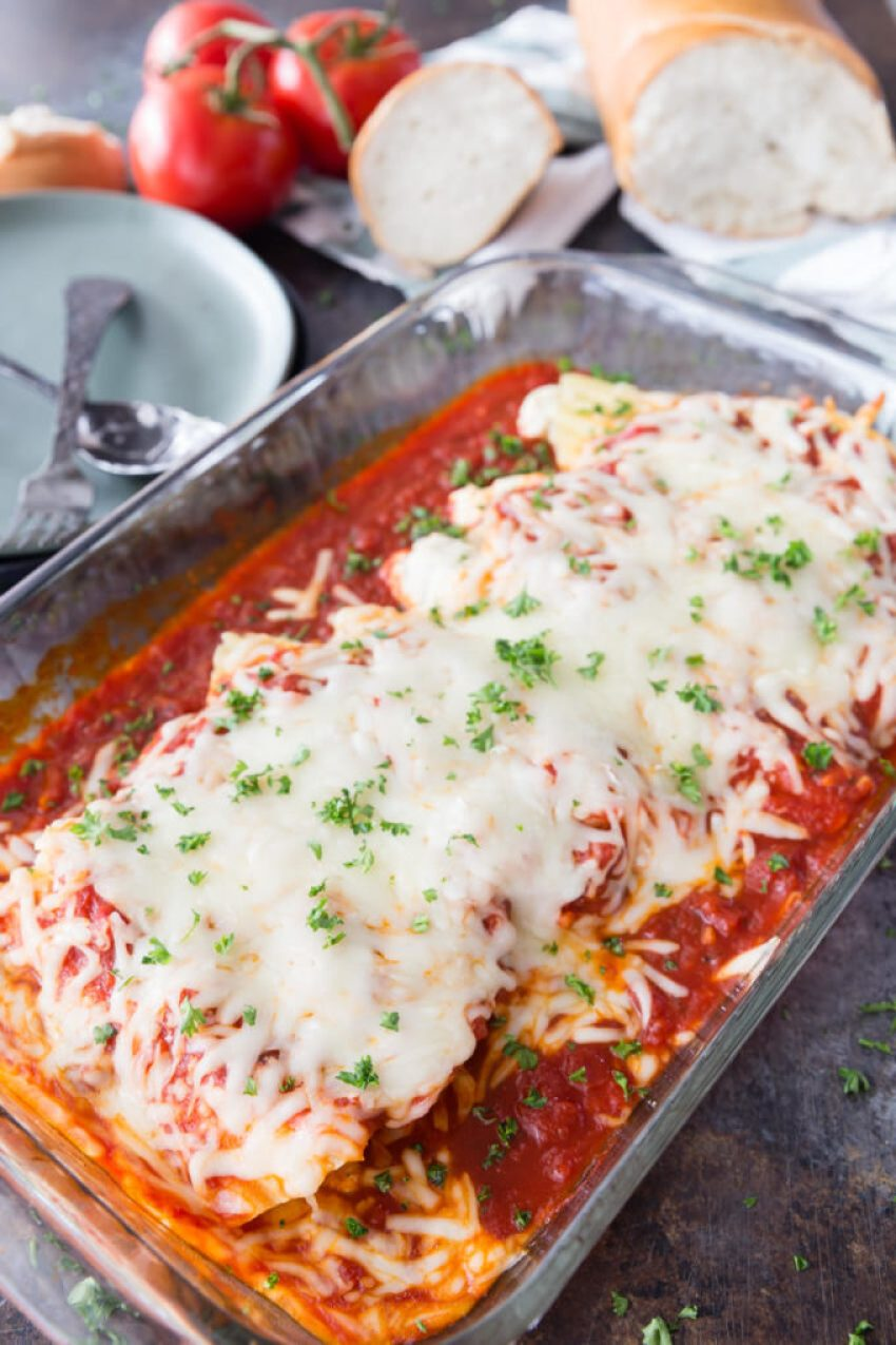 a dish of freshly baked stuffed chicken and cheese manicotti covered with pasta sauce and cheese with herbs for garnish