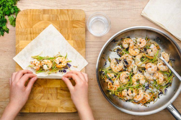 Making shrimp and veggie egg rolls