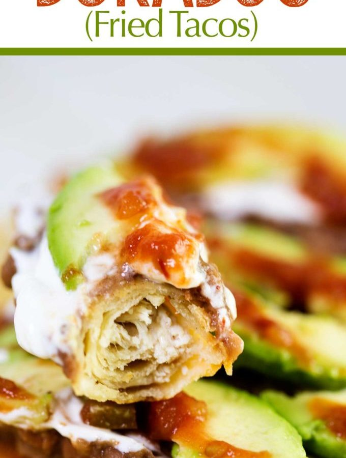 Tacos Dorados or fried tacos filled with tender chicken and cheese and topped with beans, sour cream, avocado, and salsa
