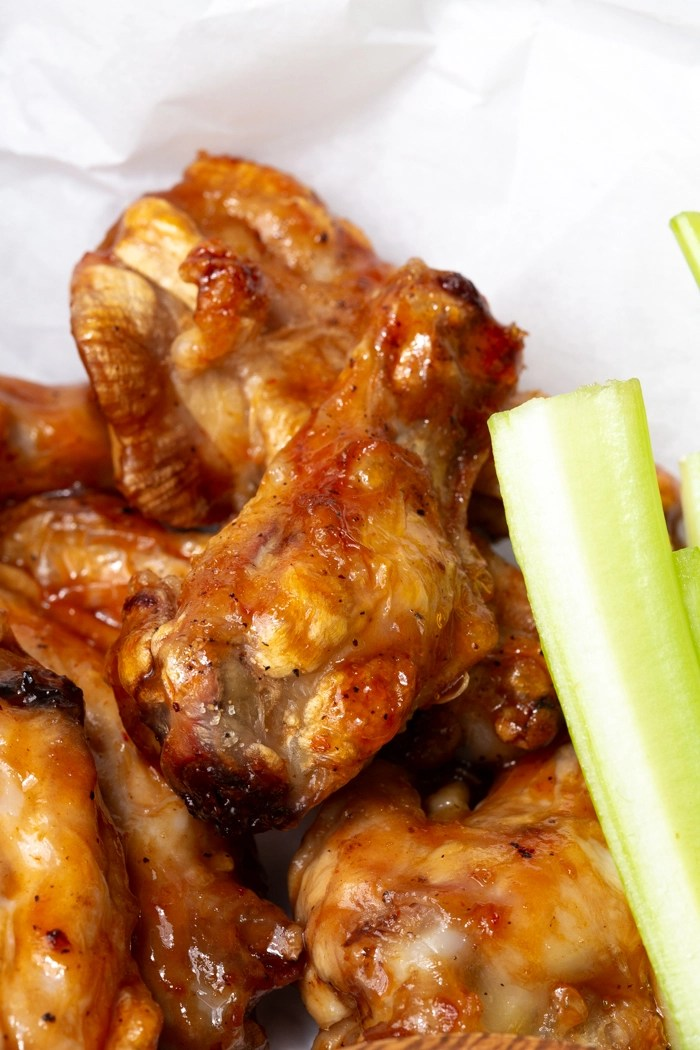 A close up of an air fryer chicken wing dipped in a great sauce