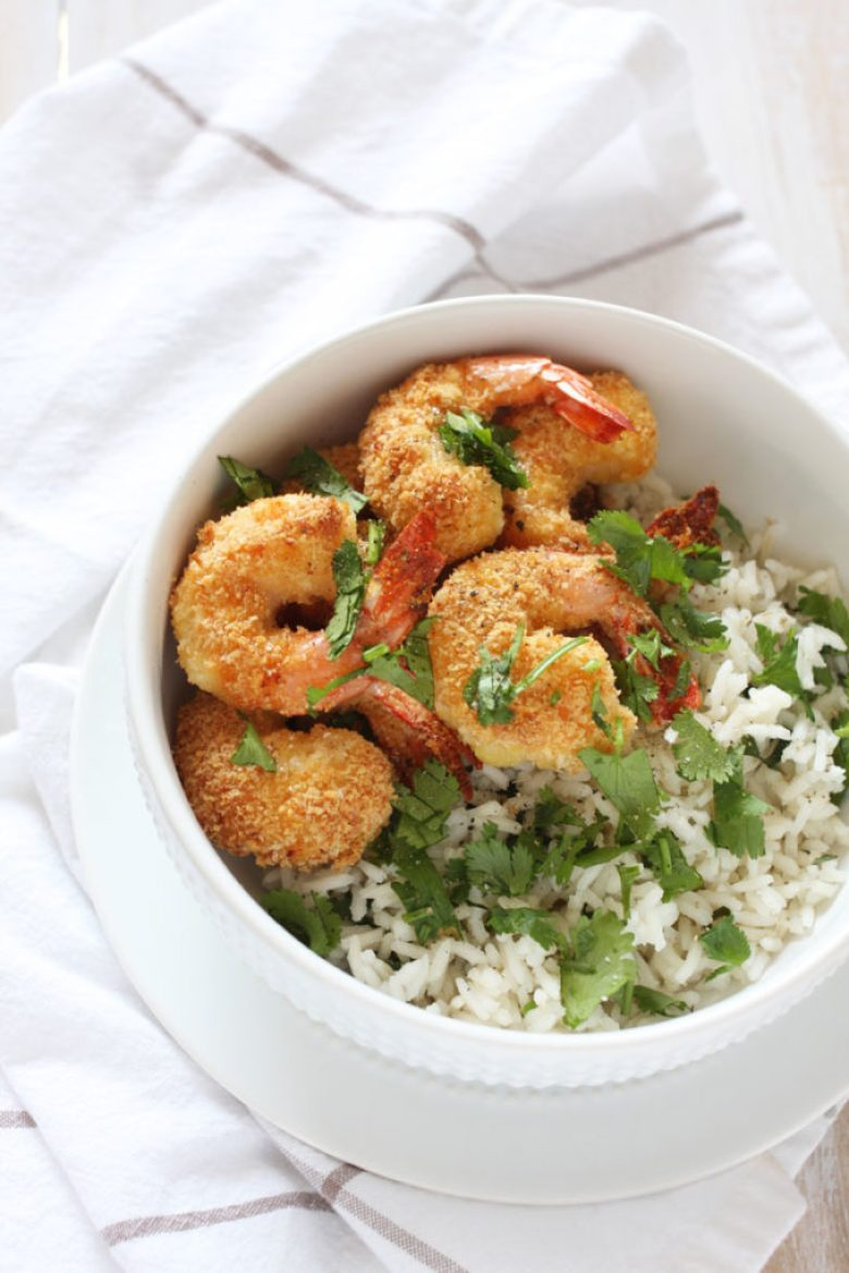 This coconut shrimp is baked in the oven for a healthier and extra crispy meal paired with rice cooked in coconut water and drenched in lime juice.