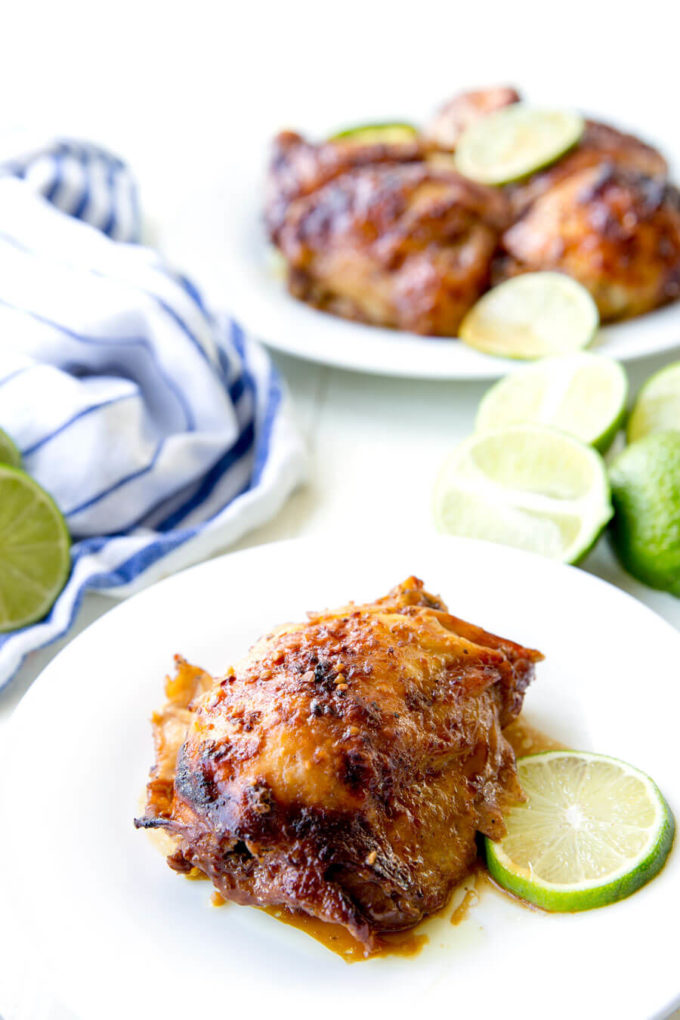 Crockpot Garlic Lime Chicken on white plate with a fresh slice of lime.